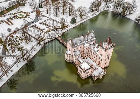 Aerial Drone Shot Of Anif Schloss Moated Castle In Artificial Pond At Salzburg Outskirts In Heavy Sn