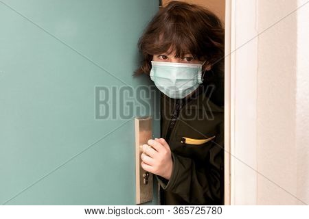 A Boy In A Surgical Mask Looks Out Of The Ajar Door. Antivirus Protection.