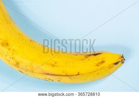 Ugly Yellow Banana With Black Spots On A Pink And Blue Background Close-up