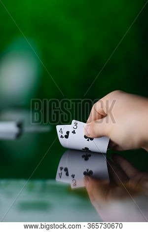 Hand Showing Two Poker Cards On The Table With Reflection On Green Background