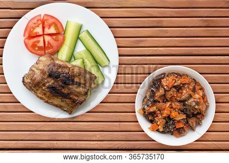 Grilled Pork Ribs With Sliced Cucumbers And Tomatoes On A White Plate. Pork Ribs On Orange Wooden Ba