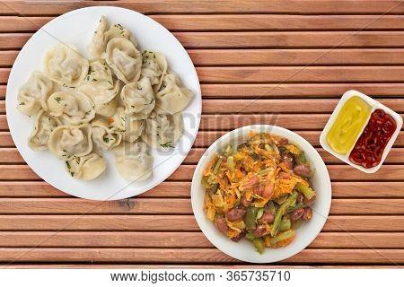 Dumplings On A White Plate On Orange Wooden Background .boiled Dumplings With Salad.meat Dumplings T