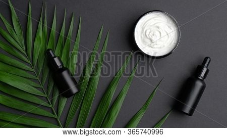 Flat Lay Composition With Black Aromatic Oil Bottles, Body Cream And Palm Leaves On Black Background