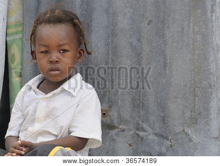Haitian kid on doorstep.