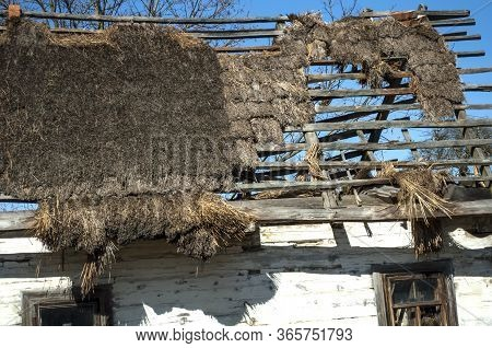 Old Dilapidated Wooden House With Whitewashed Walls And Thatched Leaky Roof Against The Sky. The Per