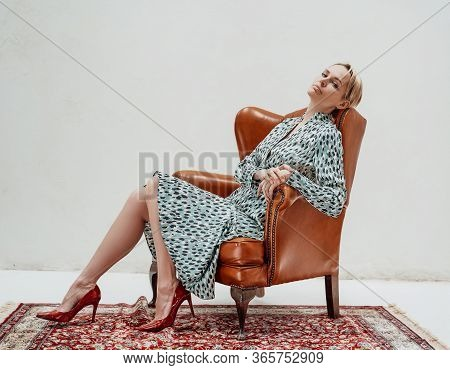 Relaxed Woman With Short Blonde Hair Is Sitting On A Leather Chair In A Bright Studio, Wearing Blue