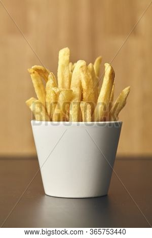 Fresh Fried French Fries In White Mug On Wooden Table. Close Up