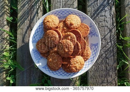 Cookies With Sesame Seeds On A White Ceramic Dish On A Wooden Board