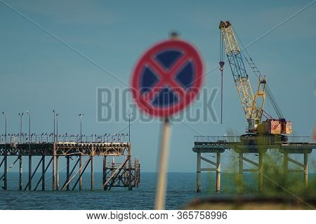 Crane Building A Fishing Pier In Turqoise Water And Demolishing The Old One