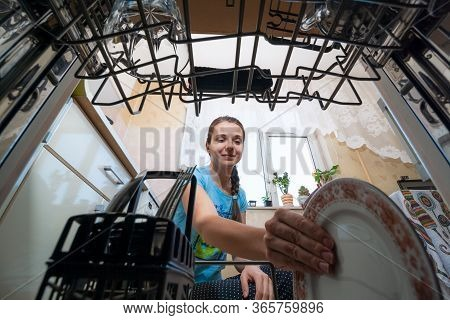 A Young Woman Putting A Plate In The Dishwasher. Inside View Of A Dishwasher. Washing Dirty Dishes A