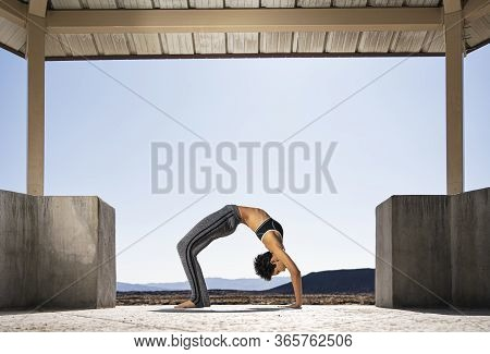A Woman Does Yoga At A Lava Field Near Amboy Crater