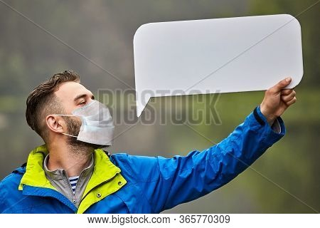 A Bearded Young Man Wearing A Protective Medical Mask Holds In His Hand An Empty Cardboard Sheet On