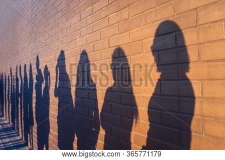 People Crowd Shadows Lined Up Against A Red Brick Wall. They Are In A Queue For Changes In Life. Soc