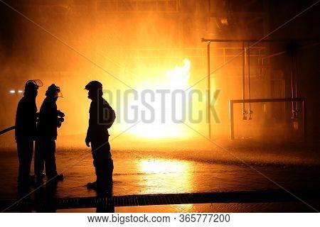 Firefighters And Rescue Training. Firefighter Spraying High Pressure Water To Fire Burning Fire Flam