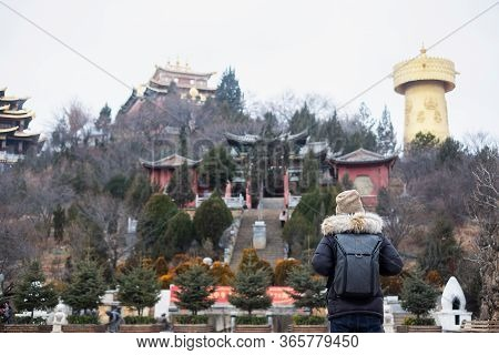 Young Man Traveler With Sweater Traveling In Shangri-la Golden Temple Or Dafo Temple With Giant Spin