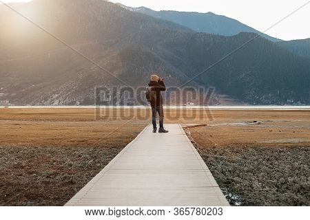 Hipster Man Traveler With Sweater And Backpack Traveling At Napa Lake, Photographer Taking Photo To