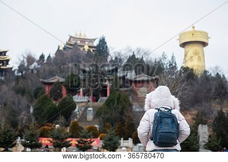 Young Woman Traveler With Sweater Traveling In Shangri-la Golden Temple Or Dafo Temple With Giant Sp