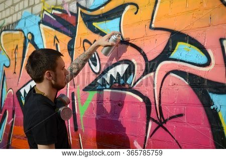 Young Graffiti Artist With Backpack And Gas Mask On His Neck Paints Colorful Graffiti In Pink Tones