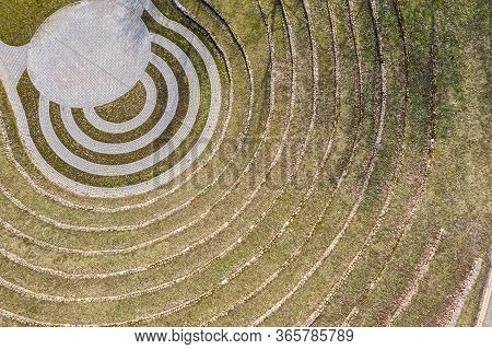 Grass And Stone Steps Of Outdoor Amphitheater At Sunny Day. Aerial Top View