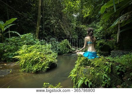 Young Caucasian Woman Sitting On The Rock, Practicing Yoga And Pranayama. Hands In Gyan Mudra. View