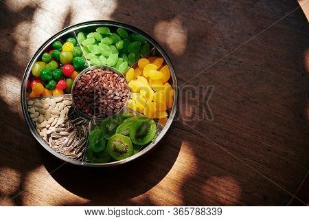 Round Plate With Seeds And Dried Sweet Fruits On Wooden Table Served For Tet Celebration