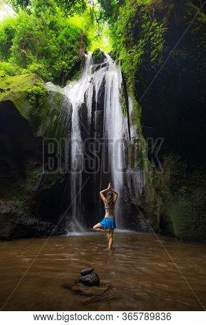 Vrikshasana Asana, Tree Pose. Young Caucasian Woman Meditating, Practicing Yoga At Waterfall. Hands