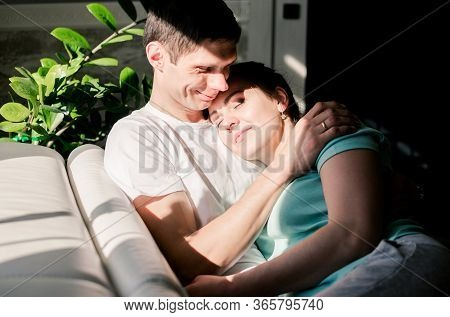 Lovers Relax On A Cozy Sofa In The Living Room, A Woman Lies On The Man S Shoulder, A Man And A Woma