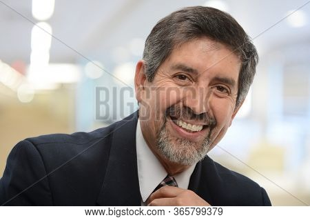 Mature latino businessman smiling inside an office building