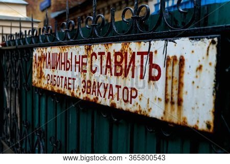 An Old Rusty Sign On A Metal Fence. Inscription On The Plate: