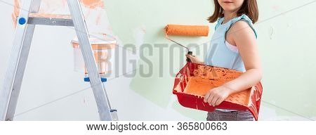 Kid Standing With Paint Roller In Hand, Close-up. She Is Painting The Wall. Redecoration, Repair And