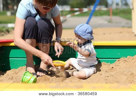 Mother and her son sifted sand in a sandbox poster