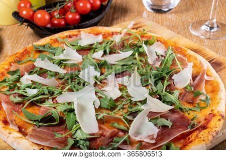 Fresh Oven Baked Traditional Prosciutto, Rucola, Tomato And Parmesan Pizza, Served On A Wooden Board