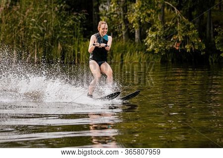 Young Woman On Water Skiing Riding On Lake In Summer