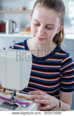 Teenage Girl Learning How To Use Sewing Machine At Home