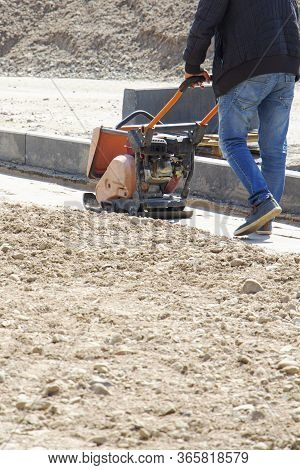 Plate Compactor For For Soil Compaction Pavement Or Sidewalk In The City. Worker Is Compacting Soil
