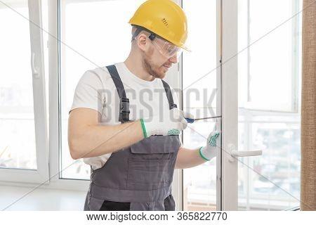 Worker Man Installs Plastic Windows White Lock And Seal Adjustment