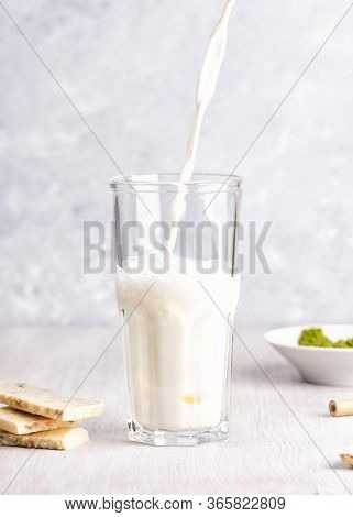 Pouring Milk Into A Glass. White Chocolate And Matcha