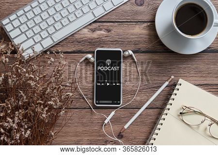Podcast Audio Content Concept. Podcast Application On Mobile Smartphone Screen On Wooden Table With