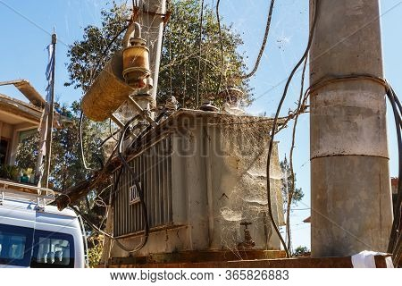 Electric Transformer On A Post In Nepal. Transformer Tangled In Spider Silk.