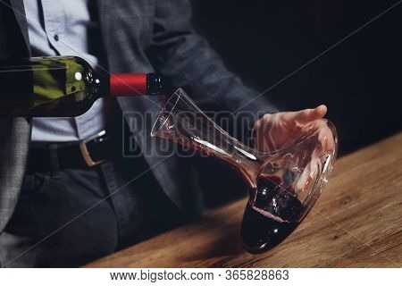 Sommelier Man Pours Red Wine Into Decanter For Aeration Of Taste And Aroma