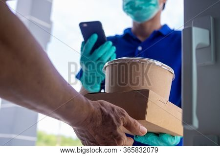 Online Orderers Accepting Food Boxes From Deliveryman Wearing Blue Uniform With Masks And Gloves. Ea
