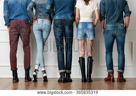 Young People's Legs In Jeans And Boots On Wooden Floor. Fashionable Clothes. Blue Denim Jeans And De