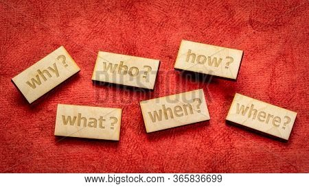 decision making or brainstorming questions - text engraved in wooden block against red textured paper background