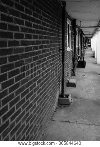 Converging lines of brick wall, on the side of building. Taken in black and white.