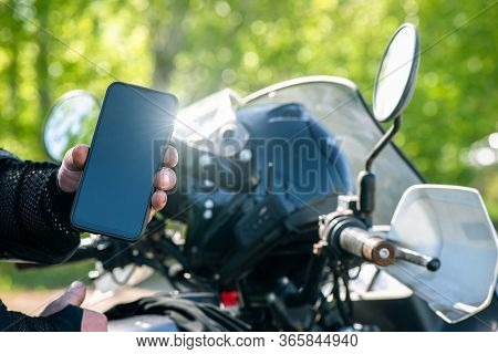 Motor Biker Is Showing In Hands A Blank Screen Mobile Phone. Online Navigator.