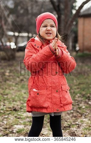 Sly Little Girl In A Jacket And Hat Rubs Her Hands, Conceived Something Insidious