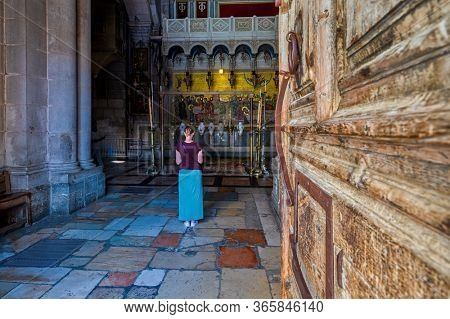 JERUSALEM, ISRAEL - JULY 14, 2019: Woman standing in front of the Stone of Anointing - the place inside of the Church of the Holy Sepulchre where Jesus' body was prepared for burial.