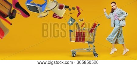 Emotional pretty girl hurries shopping with a trolley. Fashion model posing at studio in motion on a yellow background. Fashion, shopping and sale concept.