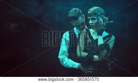 Glamorous passionate couple of a man and a woman in the style of 1920s in a dark smoky interior. Fashion clothes, make-up and hair in luxurious retro style.
