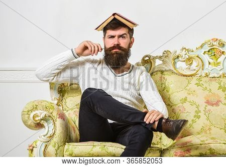 Macho Sits With Open Book On Head, Like Roof. Man With Beard And Mustache Sits On Baroque Style Sofa